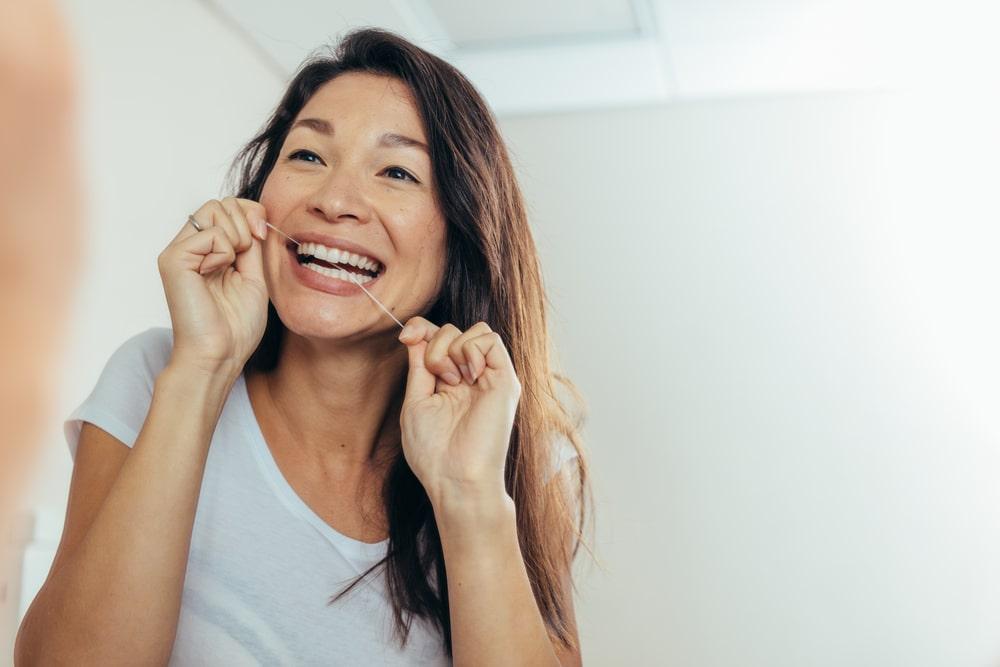 Une femme passe la soie dentaire